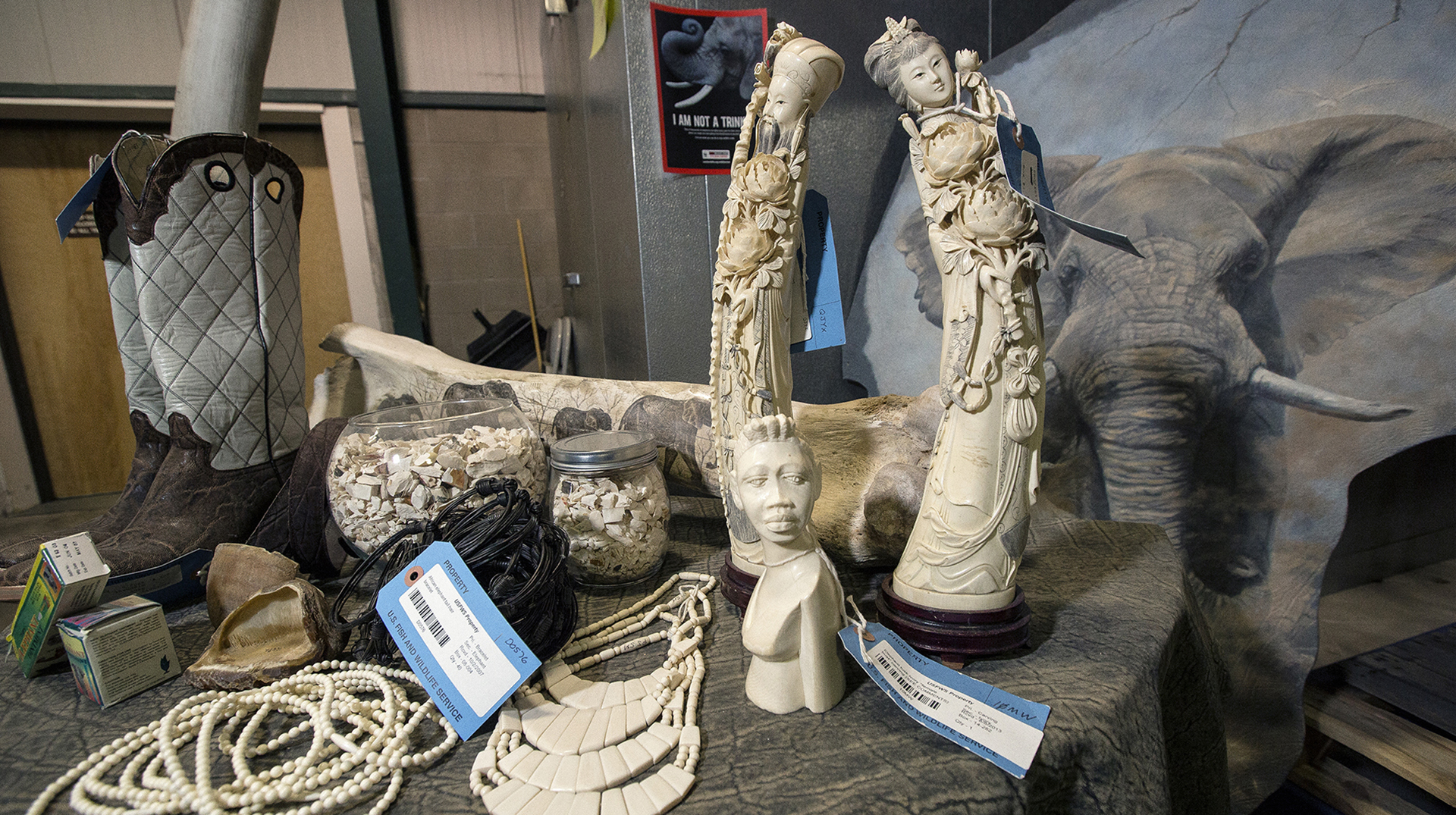 A pile of confiscated items with tags on them in including ornate objects made of ivory.
